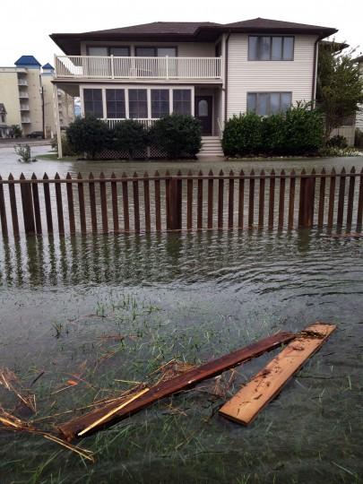 A yard is flooded along with 8th Street. (Karl Merton Ferron / Baltimore Sun)