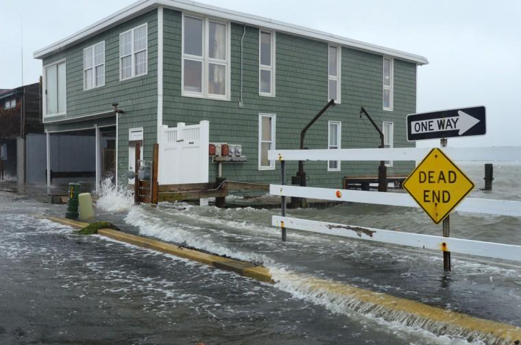 The storm surge pours onto Edgewater Avenue at 8th Street as Hurricane Sandy nears. (Karl Merton Ferron/Baltimore Sun)