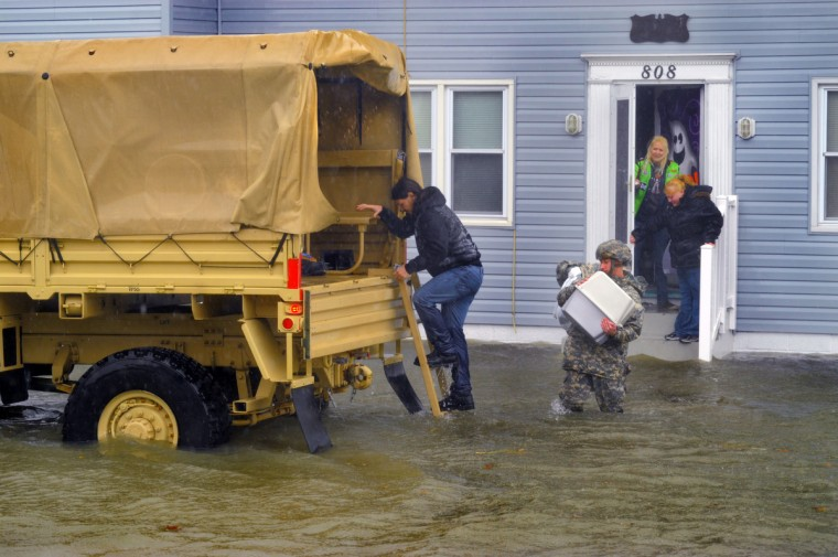 A military truck sits in the water on St. Louis Avenue between 8th and 9th Streets in Ocean City as personnel help residents evacuate with their essential belongings from their apartment. (Karl Merton Ferron/Baltimore Sun)