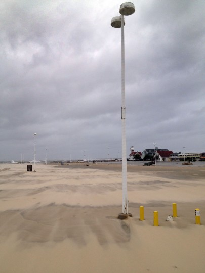 The tidal surge left beach sand covering the inlet parking lot. (Karl Merton Ferron / Baltimore Sun)