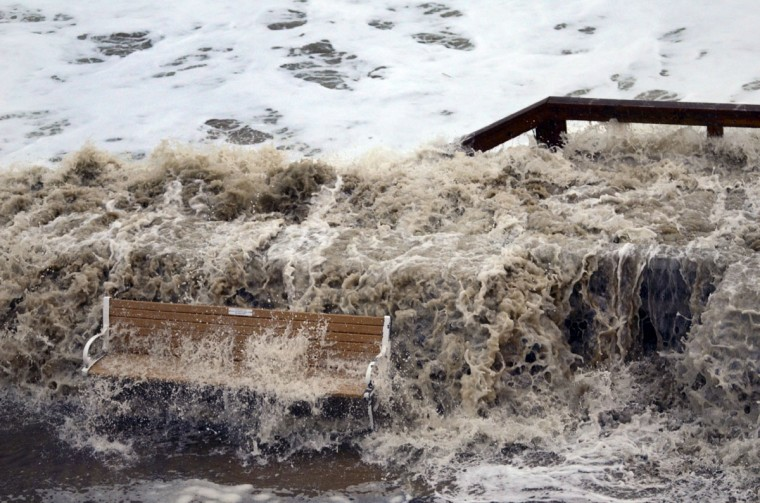 October 29, 2012: A wave crashes at the seawall, pouring over a bench on the boardwalk near 15th Street as Hurricane Sandy, now a Category One system, turns towards the eastern seaboard Monday. (Karl Merton Ferron/Baltimore Sun)