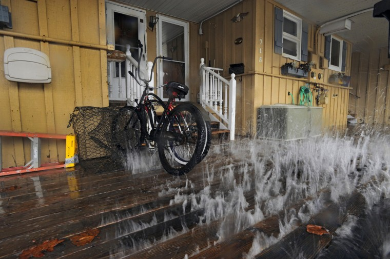 The impact of the storm effects from Hurricane Sandy, which has yet to arrive in the region creates waves that pummel the belly of the decking that squirts between the boards, spraying children's bikes that rest at the front door of an apartment on Edgewater Avenue. (Karl Merton Ferron/Baltimore Sun)