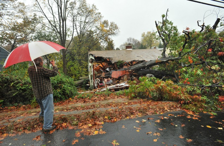 Neighbor Dee Cooke takes some snapshots of a home at 420 W. Maple Avenue that was crushed by a tree during Hurricane Sandy. (Amy Davis/Baltimore Sun)