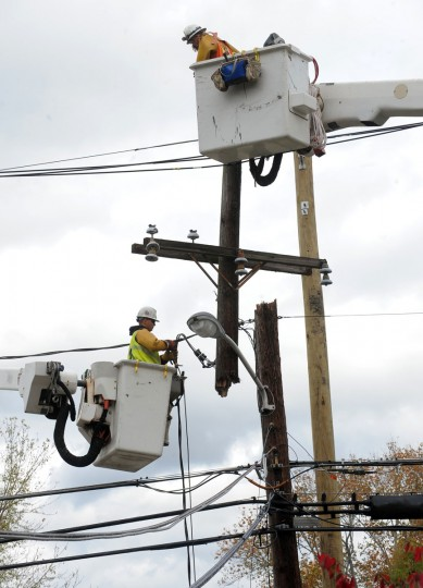 "At left, Maciej Skrzyniarz, and at right, Adam Rossman from Commonwealth Edison, which, like BGE, is owned by Exelon Corporation, remove a snapped telephone pole and replaces it with the pole at right, at the corner of Hilton Ave. and Ridge Rd. The work crew traveled from Northern Illinois to repair the damage from ""superstorm"" Sandy. (Algerina Perna/Baltimore Sun)"