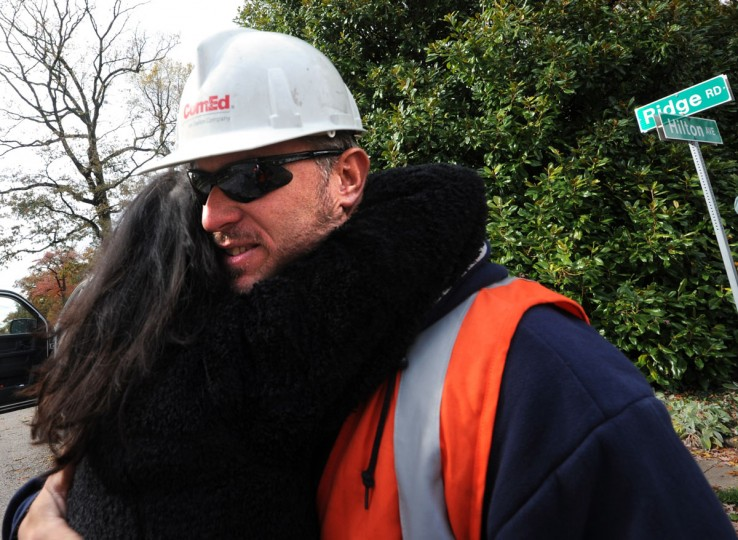 "Jennifer Parker hugs Eric Bannon with Commonwealth Edison, which, like BGE, is owned by Exelon Corporation, is the company fixing downed wires and telephone poles at the corner of Hilton Ave. and Ridge Rd. She and Ken Erickson brought snacks and drinks to Bannon and other workers. ""We're so appreciative that they're here, she says. ComEd, which has merged with BGE, fixes a snapped telephone pole at the corner of Hilton Ave. and Ridge Rd. The work crew traveled from Northern Illinois to repair the damage from ""superstorm"" Sandy. (Algerina Perna/Baltimore Sun Photographer)"