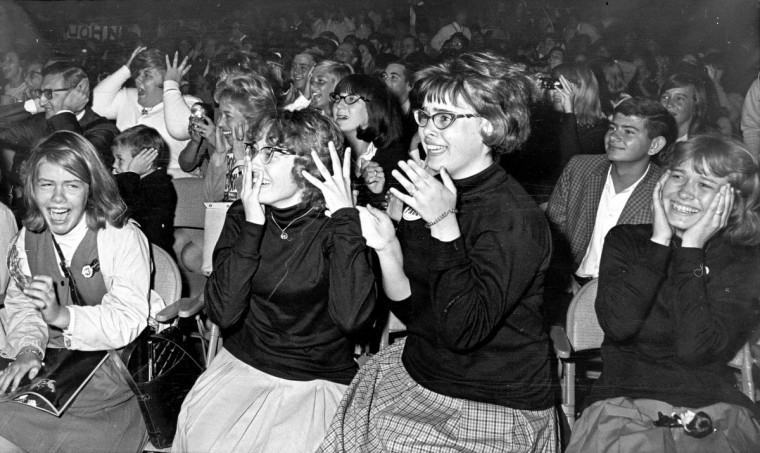 09/13/64 - Surrounded by a sea of Beatles fans at today's performance, a man and boy (upper left) seem to be trying to shut out the din of music and shrieks in the Baltimore Civic Center. Witnesses said it was impossible. No injuries were reported. (Baltimore Sun)
