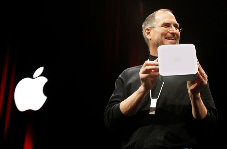 January 11, 2005: Apple Computer Inc. CEO Steve Jobs unveils the new Mini Mac while wearing the new iPod Shuffle around his neck after giving the keynote address during the Macworld Conference and Expo at the Moscone Center Esplanade in San Francisco, California. (Jeff Chiu/AP Photo)