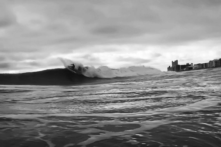 """Sixteen-year-old Brad Flora does a """"hack"""" on a good sized wave last winter. Denny says, """"This day was really hard to line up a shot so I used a 50mm lens. The current was so bad I drifted like 15 streets in 30 minutes."""" (Credit: Nick Denny)"""