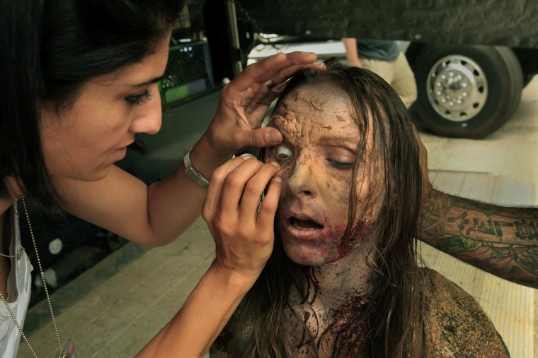 "Amanda Adams has a fake eye put on her as she is made up for the role of a zombie on the set of ""The Walking Dead,"" the zombie series on AMC, in June 2012. (Carolyn Cole/Los Angeles Times/MCT)"