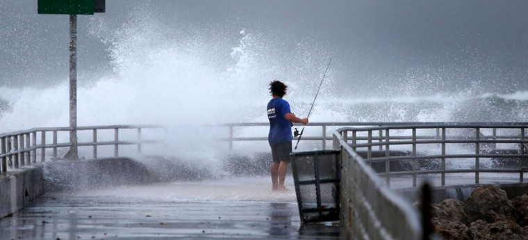 October 26, 2012: Eric Peterson, of Tequesta, casts his line and shoots some video of the waves on the fishing jetty at the Jupiter Inlet on Friday. (Lannis Waters/Palm Beach Post/MCT)
