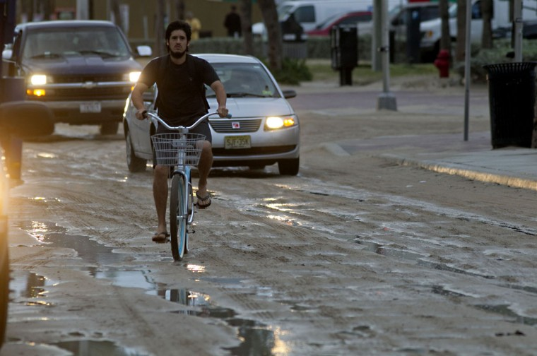 October 26, 2012: Cars and bikes navigate sand on A1A from high tides and wind driven waves at Ft. Lauderdale Beach, Florida, Friday. (Joe Rimkus Jr./Miami Herald/MCT)