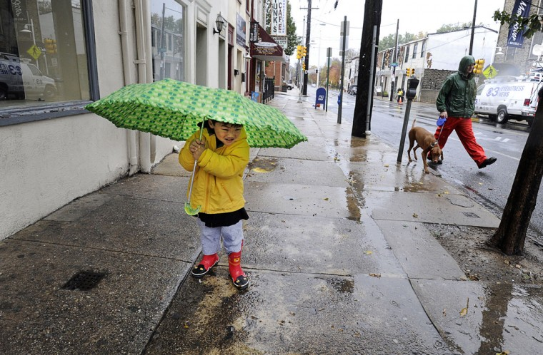 October 29, 2012: As the winds of hurricane Sandy blow across the region, Parker Kim, 3 years old, holds on as tight as he can to his umbrella on Main Street in Manayunk section of Philadelphia on Monday. He and his mother were walking looking for puddles for Parker to jump in. (Sharon Gekoski-Kimmel/Philadelphia Inquirer/MCT)