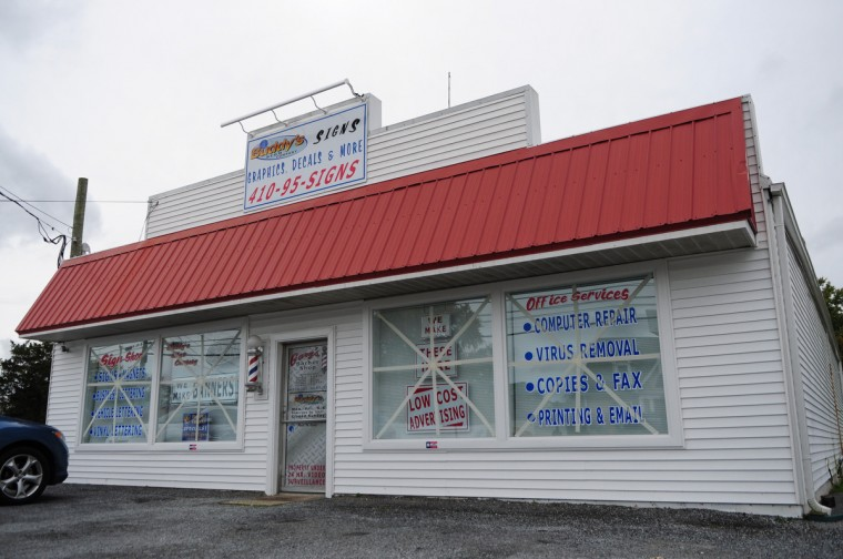 Buddy's Sign Shop in Pocomoke started making preparations for the arrival of Hurricane Sandy by taping up their storefront windows. (Patricia Hildenbrand/Daily TImes)