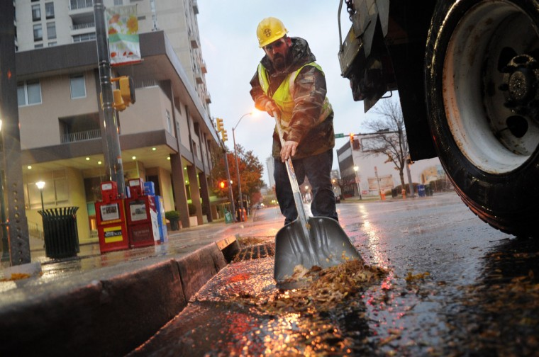 Joey Atwell with Baltimore County Highway Public Works clears leaves and other debris from a storm drain on Allegheny Avenue ,allowing the rushing rain water to flow more freely, as the effects of Hurricane Sandy were felt in and around Towson, Md., on Monday. (Brian Krista/Patuxent Homestead)