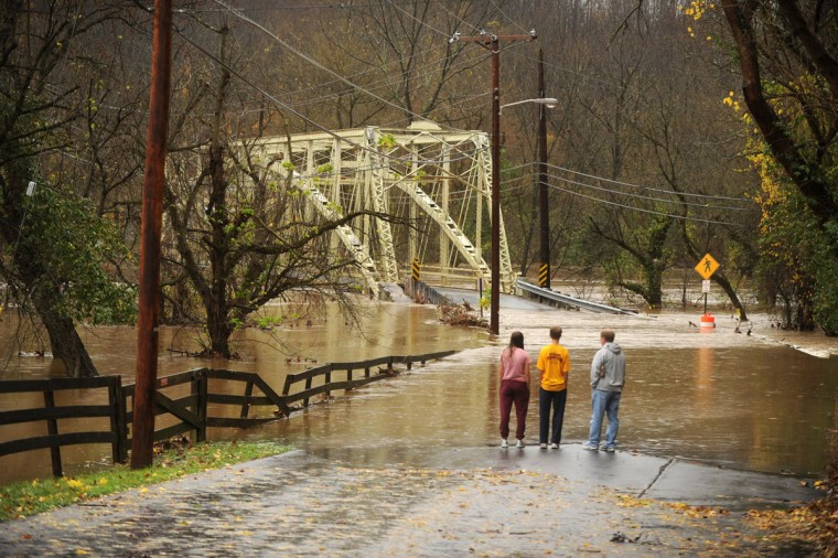 October 30, 2012: Mike Gibson of Monkton, right, watches with his daughter Maddy, left, and son Cooper as Gunpowder Falls overflows its banks and overtakes a stretch of Sparks Road as a result of Hurricane Sandy in Cockeysville, Md., on Tuesday. (Brian Krista/Patuxent Publishing)