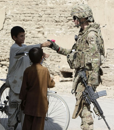 A boy gives a flower to U.S. army soldier SGT Jessica Corona of Task Force Lancer, 563 Military Police Company while on patrol in Kandahar city, southern Afghanistan. (Erik De Castro/Reuters)
