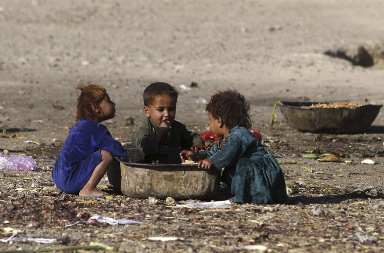 Afghan internal displaced refugee children eat food near their shelter at the outskirts of Kabul. (Omar Sobhani/Reuters)