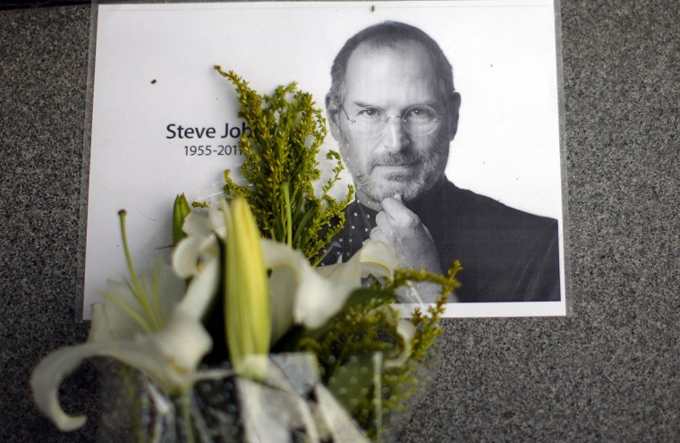 October 6, 2011: Flowers for Apple co-founder Steve Jobs are seen outside an Apple Store in downtown Shanghai. (Carlos Barria/Reuters)