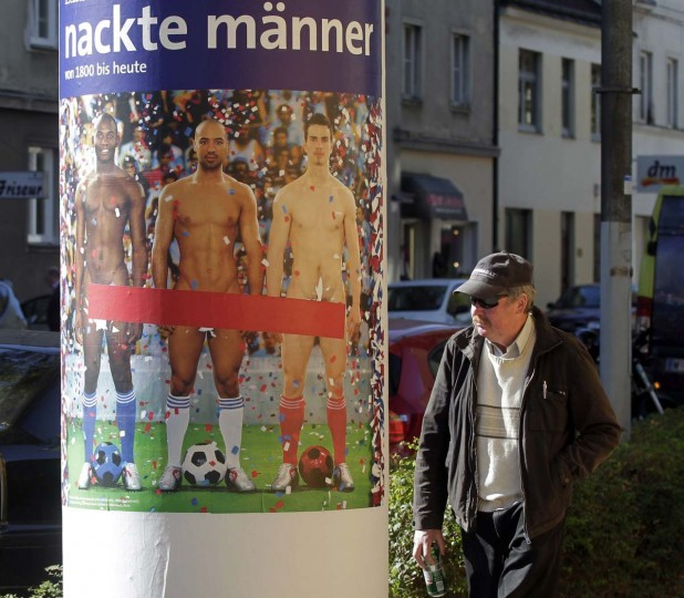 """A police officer stands next to a poster with naked soccer players daubed with spray paint, advertising an art exhibition in Vienna October 17, 2012. Vienna's Leopold Museum has decided to cover the """"intimate parts"""" of three naked male soccer players on large posters put up in the Austrian capital after they caused an outcry. The 'Naked Men' exhibition, which opens on Friday and runs until January 28, 2013, is designed to show how the depiction of male nudity has evolved in art history. Around 300 art works - including the controversial photograph by French artists Pierre & Gilles called 'Vive La France' of three men of different races wearing nothing but blue, white and red socks and soccer boots - will be on display. (/Herwig Prammer/Reuters)"""