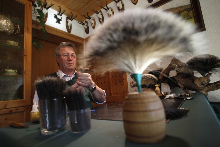 Bertl Lahnsteiner works on a 'Gamsbart', a decoration for traditional alpine hats, at his home in Offensee in Austria's Salzkammergut area October 8, 2012. A 'Gamsbart', a tuft of neck-hair from the chamois, a European mountain goat, originally was the trophy of the dear hunter after successful shooting game. (Herwig Prammer/Reuters)