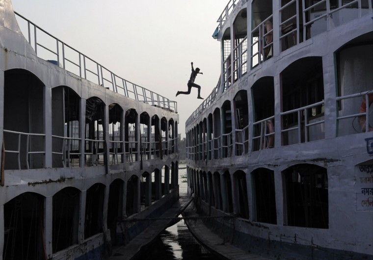 A man jumps from a boat to another by the river Buriganga in Dhaka October 16, 2012. (Andrew Biraj/Reuters)