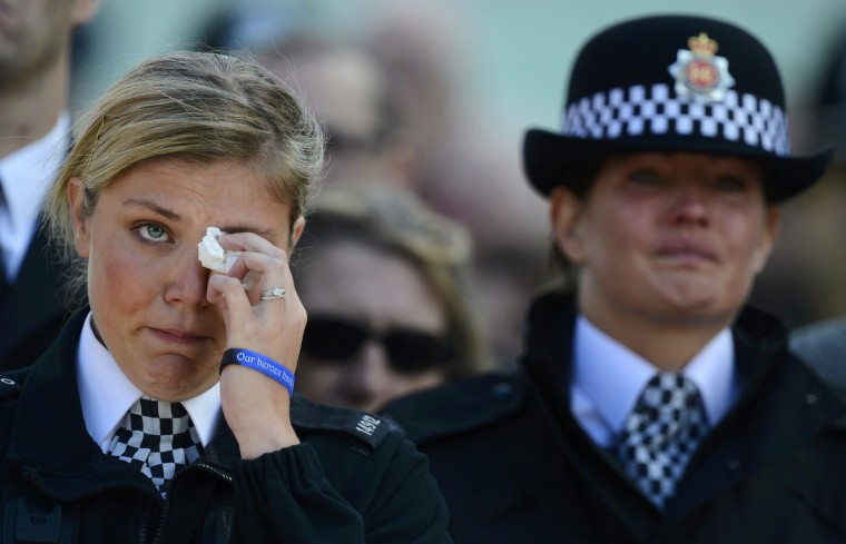 A police officer cries as the coffin of Greater Manchester Police constable Nicola Hughes is carried into Manchester Cathedral for her funeral service in Manchester, northern England. Hughes and fellow officer pc Fiona Bone were shot and killed in a gun and grenade attack in Hattersley near Manchester on September 18. (Nigel Roddis/Reuters)