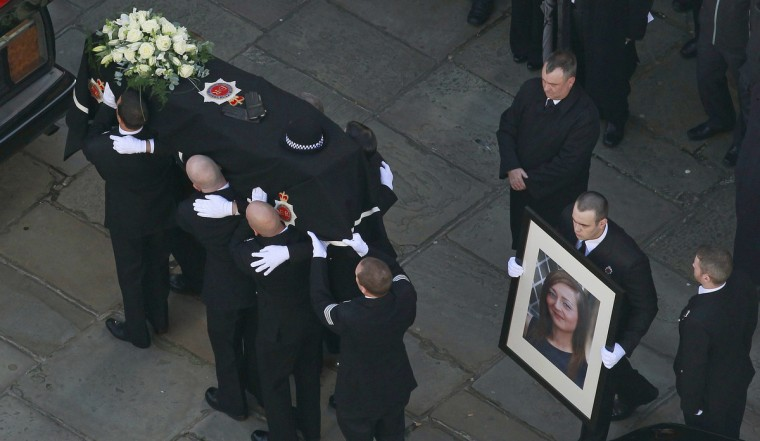 Police officers carry the coffin of Greater Manchester Police constable Nicola Hughes into Manchester Cathedral for her funeral service in Manchester, northern England. Hughes and fellow officer pc Fiona Bone were shot and killed in a gun and grenade attack in Hattersley near Manchester on September 18. (Cathal McNaughton/Reuters)