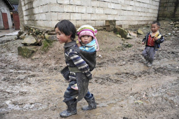 A Yi ethnic minority girl carries her younger sister on her back as she walks amid a muddy road at Butuo county of Liangshan Yi Autonomous Prefecture, Sichuan province. Locked in deep mountains, Liangshan Yi Autonomous Prefecture is the biggest inhabitance region for Chinese Yi minorities, as well as one of the poorest regions in China, according to local media. (China Daily)