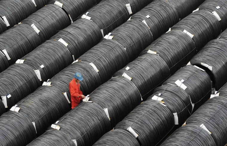 A worker checks on coils of steel at a factory in Dalian, Liaoning province. China's economy slowed for a seventh straight quarter in July-September, missing the government's target for the first time since the depths of the global financial crisis, but other data released on Thursday pointed to a year-end rebound. (China Daily/via Reuters)