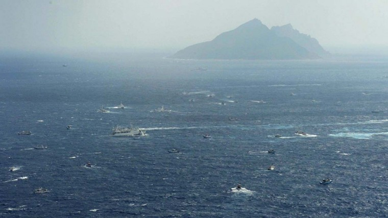 An aerial view shows a Japan Coast Guard patrol ship, fishing boats from Taiwan and Taiwan's Coast Guard vessel sailing side by side near Uotsuri island (top), a part of the disputed islands in the East China Sea, known as Senkaku in Japan, Diaoyu in China and Tiaoyutai in Taiwan, in this photo taken by Kyodo September 25, 2012. (Kyodo/Reuters)