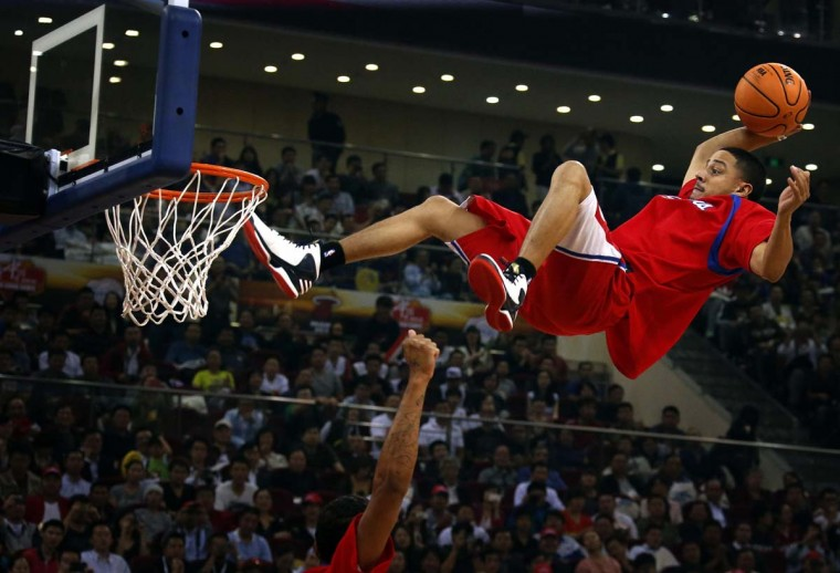A stunt performer prepares to dunk during a break in the first of the NBA China Games between the Miami Heat and the Los Angeles Clippers at Wukesong arena in Beijing. (David Gray/Reuters photo)