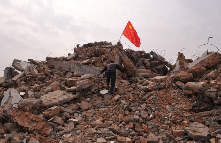 A local resident climbs towards a Chinese national flag planted at the top of his former house, which was demolished to make way for a new residential complex in Xi'an, Shaanxi province. Investment in the property sector accounted for 13.6 percent of China's gross domestic product in the first half of 2012. (Rooney Chen/Reuters)