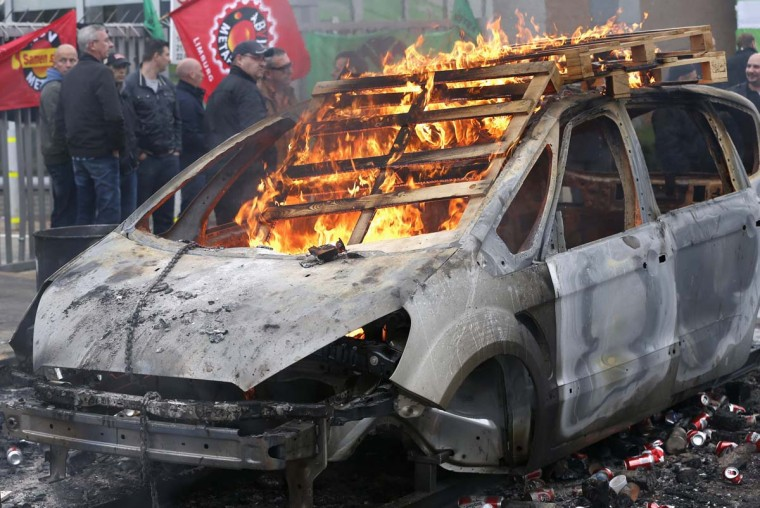 A Ford car body burns after it was set on fire by workers during a protest at the Ford assembly plant in Genk, Belgium. Ford Motor Co announced to unions on Wednesday that it will close the factory employing 4,300 workers in the Belgian town of Genk, as it tries to stem losses in Europe and match capacity to tumbling demand. (Francois Lenoir/Reuters photo)