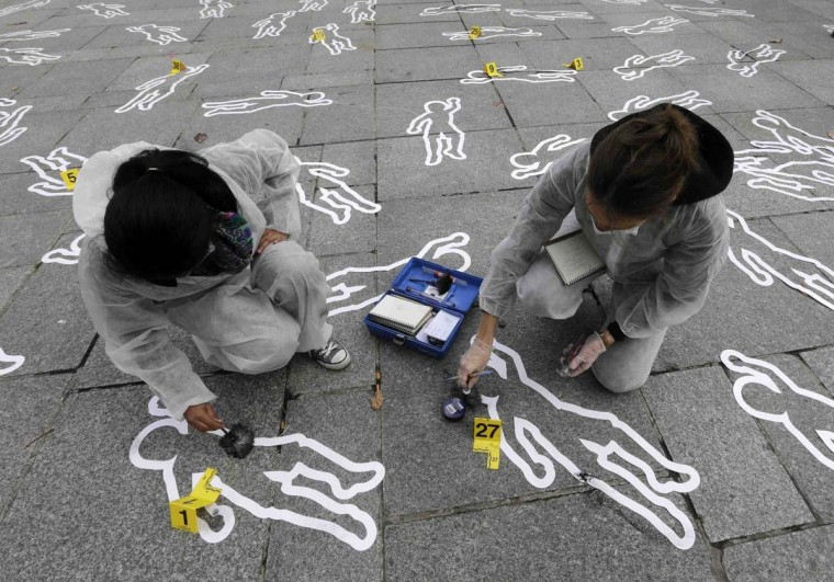 Members of the French non-government organization (NGO) Action Contre la Faim (Action Against Hunger) take part in a protest, featuring mock crime scenes, denouncing malnutrition in the world, at the Place Saint Sulpice in Paris October 15, 2012. (Jacky Naegelen/Reuters)