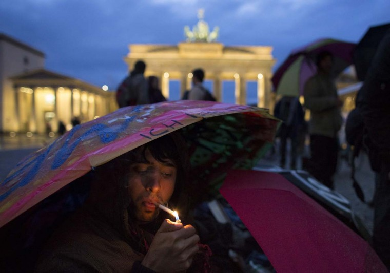 Afghan refugee Maiwand smokes a cigarette as he sits under an umbrella in front of Brandenburg Gate during a hunger strike in Berlin. Some 20 refugees, mainly from Iran and Afghanistan, went on hunger strike on October 24 demanding an end to deportations, obligatory camp accommodation to be abolished and restrictions on their movements be lifted, the refugees said. (Thomas Peter/Reuters)