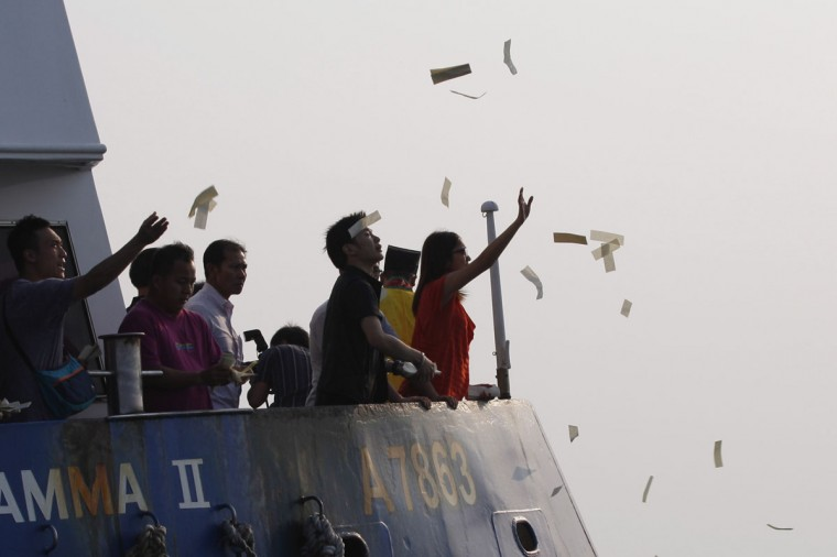Relatives of victims in a fatal ferry collision pay their respects by throwing paper money into the waters off Hong Kong. (Tyrone Siu/Reuters)