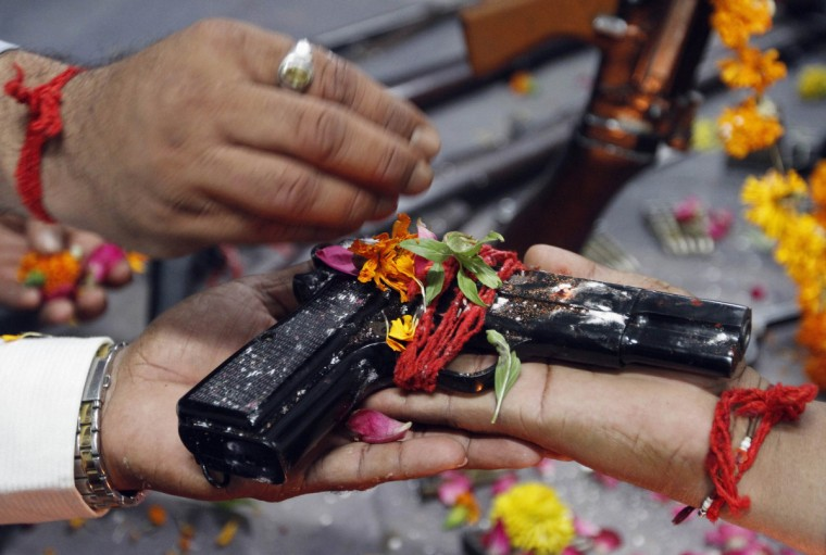 Police officers hold a 9mm pistol as they offer prayers in front of weapons, as part of a ritual for the Dussehra festival in the western Indian city of Ahmedabad. Dussehra is the Hindu festival which commemorates the triumph of Lord Rama over Ravana, marking the victory of good over evil. (Amit Dave/Reuters)