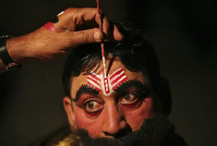"Kulbhushan, 38, a performer, gets makeup applied backstage before performing the role of the demon king Ravana in a religious play, as part of Dussehra festival celebrations in Jammu. Effigies of the 10-headed Demon King ""Ravana"" are burnt on Dussehra, the Hindu festival that commemorates the triumph of Lord Rama over Ravana, marking the victory of good over evil. (Mukesh Gupta/Reuters)"