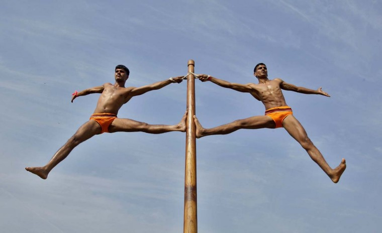 "Indian army soldiers perform ""Malkhamb"" (traditional Indian gymnastics) during a two-day army exhibition in the northern Indian city of Allahabad October 21, 2012. Malkhamb is a combination of traditional Indian gymnastics and martial arts and it can be traced back to the 12th century. (Jitendra Prakash/Reuters)"