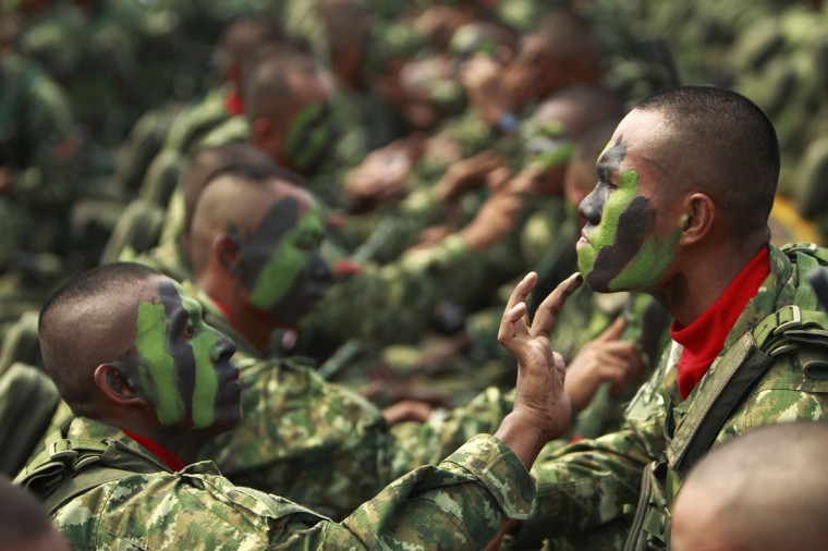 Indonesia's Airborne 328 soldier help one another apply camouflage paint on their faces before a ceremony to mark the 67th anniversary of the Indonesian National Military at the tarmac of Halim Perdanakusuma airport in Jakarta. (Beawiharta/Reuters)
