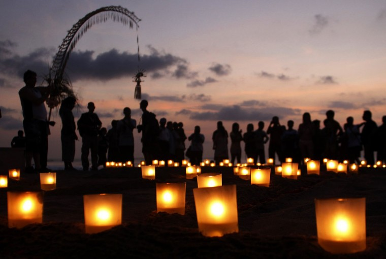 People gather around lit-up candles at Kuta Beach in remembrance of the victims of the Bali Bombing during the 10th anniversary of the incident, in Kuta, Bali. (Murdani Usman/Reuters)