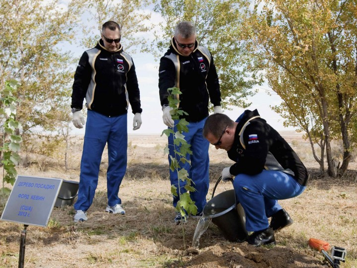 """October 17, 2012: Russian cosmonauts Evgeny Tarelkin (L), Oleg Novitskiy (C) and NASA astronaut Kevin Ford plant a tree at Baikonur cosmodrome. The board reads """"The tree planted by Ford Kevin (USA) 2012."""" (Sergei Remezov/Reuters)"""