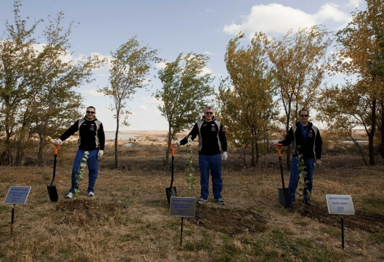 October 17, 2012: Russian cosmonauts Evgeniy Tarelkin (L), Oleg Novitskiy (C) and NASA astronaut Kevin Ford pose for a picture as they plant trees at Baikonur cosmodrome. (Sergei Remezov/Reuters)