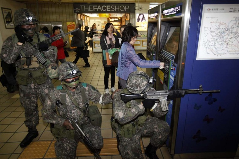 A woman uses a ticket vending machine as South Korean soldiers take part in an anti-terror and security drill at a subway station in Seoul. (Kim Hong-Ji/Reuters)