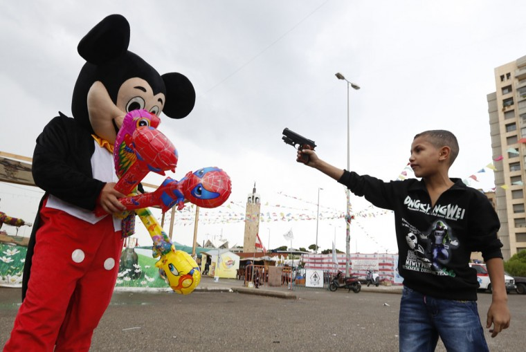A Syrian refugee boy points a plastic toy pistol at a man in a Mickey Mouse costume on the first day of Eid al-Adha at a park in Beirut. (Jamal Saidi/Reuters)