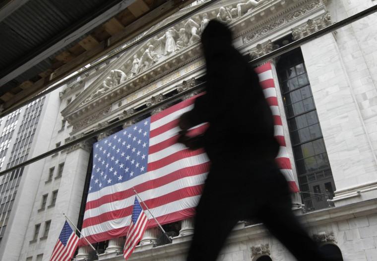 Morning commuters walk past the New York Stock Exchange. (Brendan McDermid/Reuters)