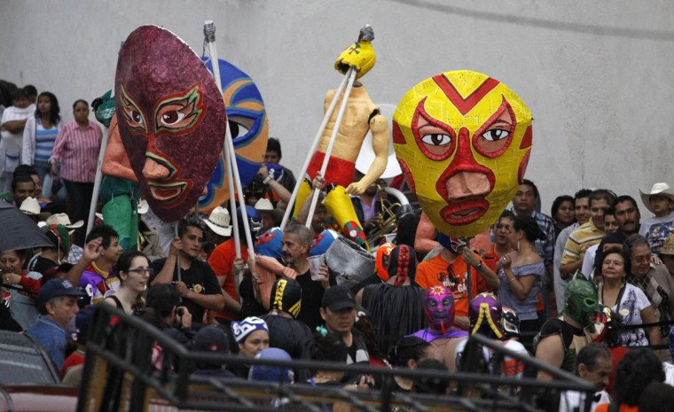 Residents hold up giant paper masks of wrestlers during festivities for Saint Michael the Archangel in the town of Zacualpan de Amilpas, on the outskirts of Cuernavaca, September 30, 2012. According to local media, the community held a carnival in honor of their patron, Saint Michael the Archangel, to thank him for the autumn harvest. (Margarito Perez Retana/Reuters)