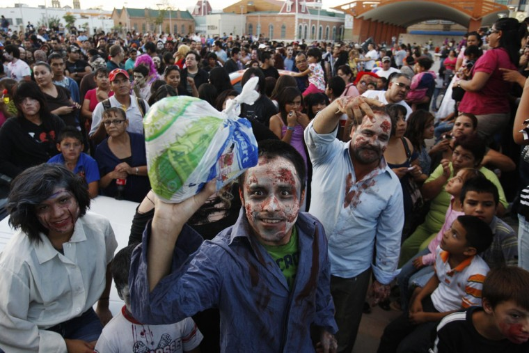"A man dressed up as a zombie holds up a bag with food during a ""zombie walk"" in Ciudad Juarez, Mexico. Children and adults dressing up as zombies took part in the ""Zombie Walk Ciudad Juarez"" on October 20, 2012, aimed at collecting food and hygiene kits to support a community center which helps children in this border city, local media reported. (Jose Luis Gonzalez/Reuters)"