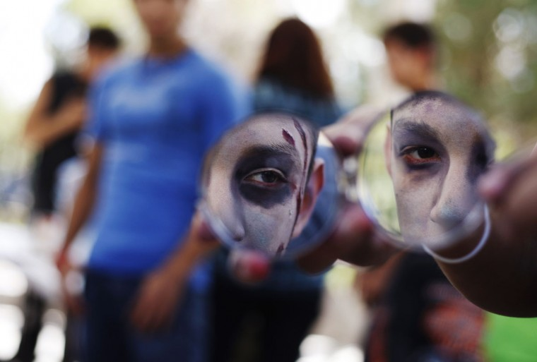 "A child looks in the mirror after applying zombie makeup before the ""Zombie Walk Ciudad Juarez."" Children and adults dressing up as zombies took part in the event, aimed at collecting food and hygiene kits to support a community center which helps children in the border city. (Jose Luis Gonzalez/Reuters)"