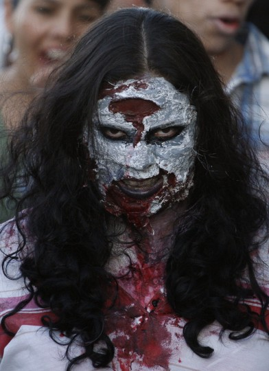 "A woman dressed up as a zombie participates in a ""zombie walk"" in Ciudad Juarez, Mexico. Children and adults dressing up as zombies took part in the ""Zombie Walk Ciudad Juarez"", aimed at collecting food and hygiene kits to support a community center which helps children in the border city. (Jose Luis Gonzalez/Reuters)"